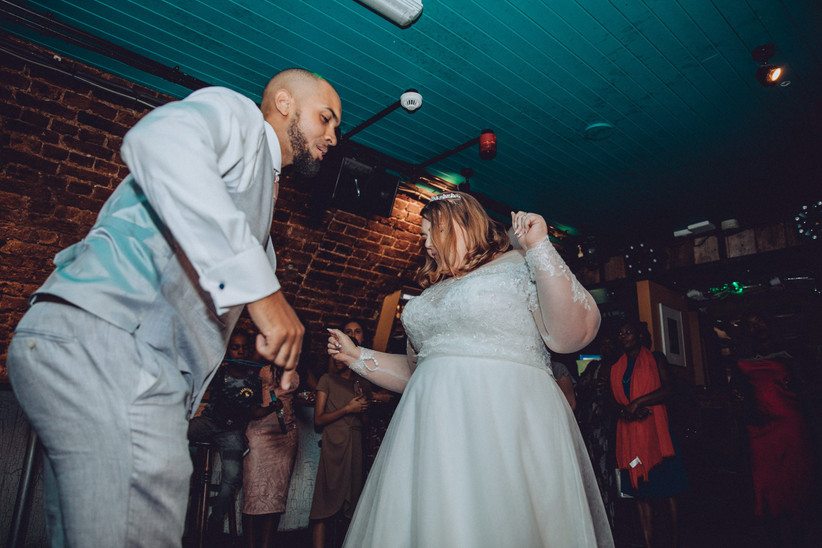 Plus size bride and groom dancing