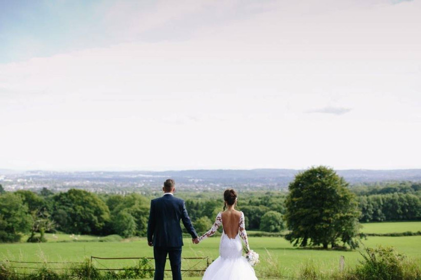 Bride and groom hold hands overlooking the countryside