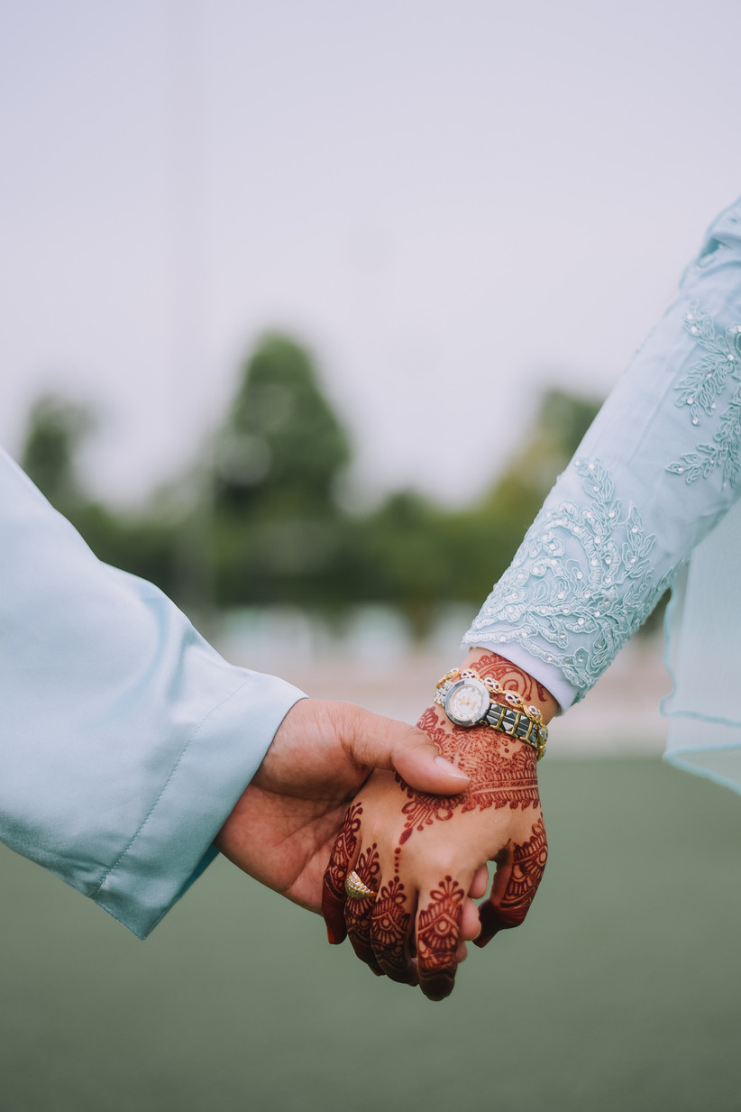 Man in a light blue suit holding the hand of a woman in a sparkly light blue top with red henna on her hands wearing a chunky silver ring, watch and a gold bracelet