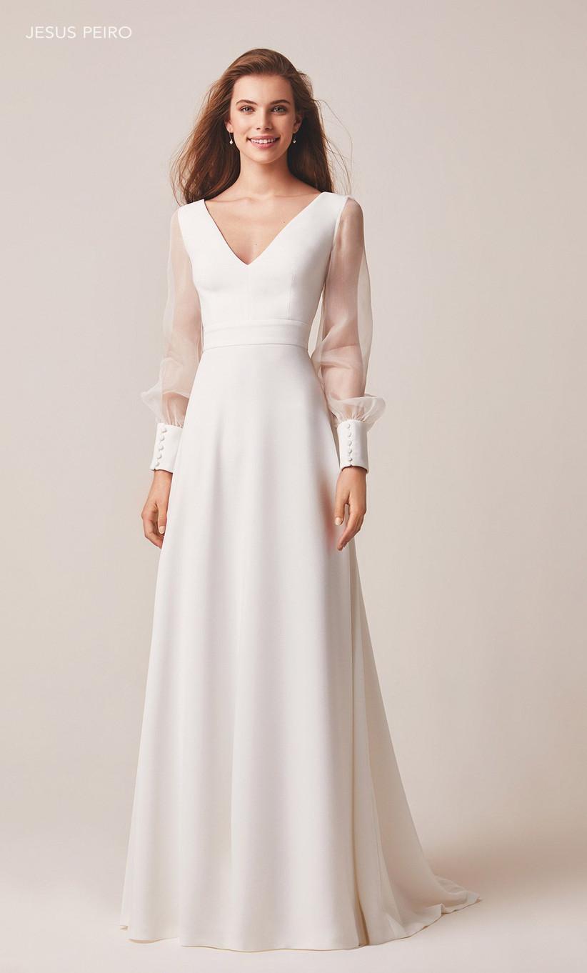 Model wearing a sheer long sleeved wedding dress