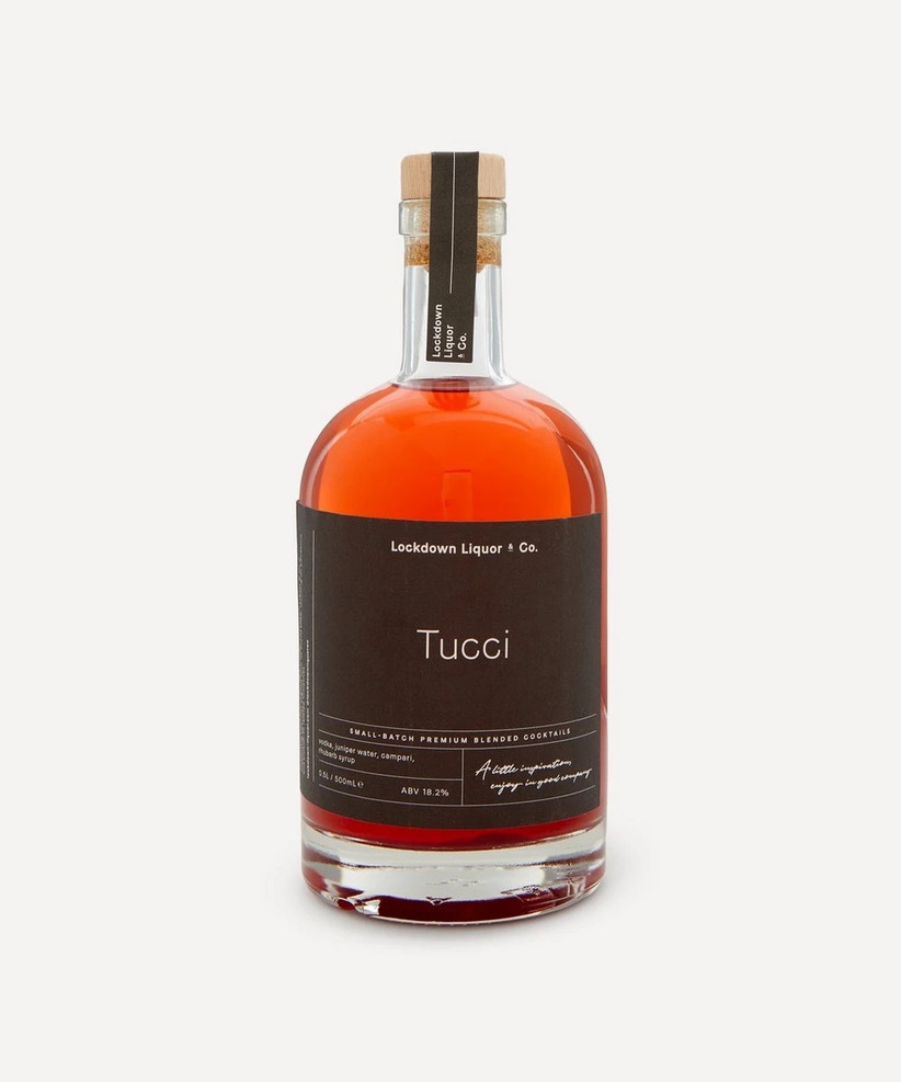 Bottle of red toned Tucci cocktail with a black and white label