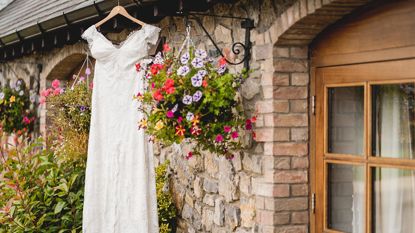 White wedding dress hanging outside a stone building