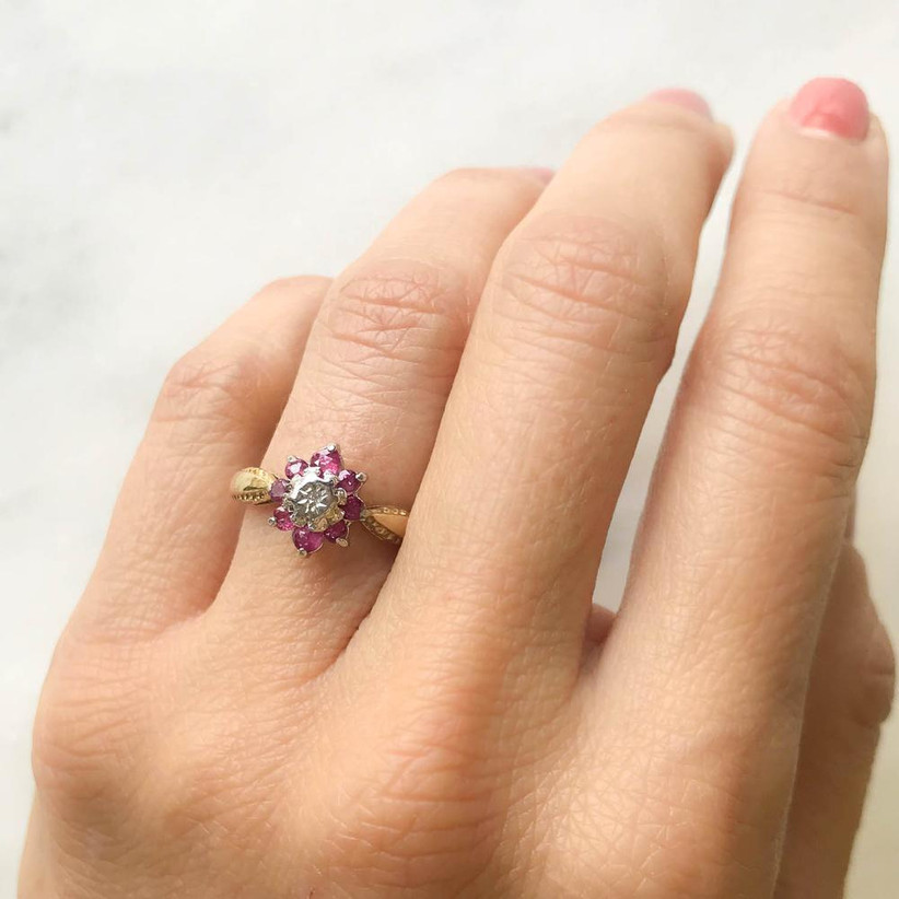 Close up of woman's hand wearing a floral style ring with ruby petals and a single diamond at the centre and a diamond studded twisted gold band