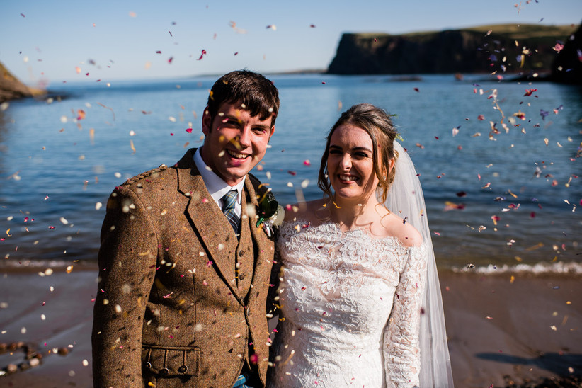 Caitlin and Stephen with colourful confetti falling around them on the beach