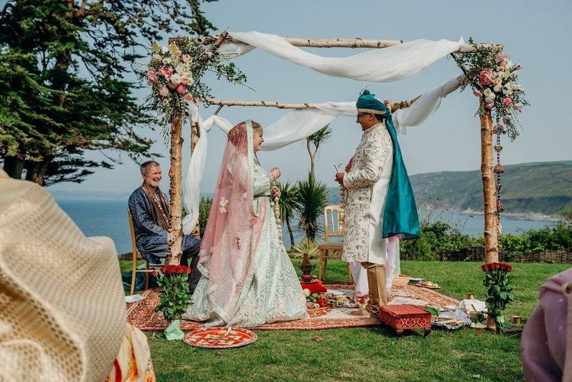 Bride and groom at an outside wedding ceremony with floral decorations