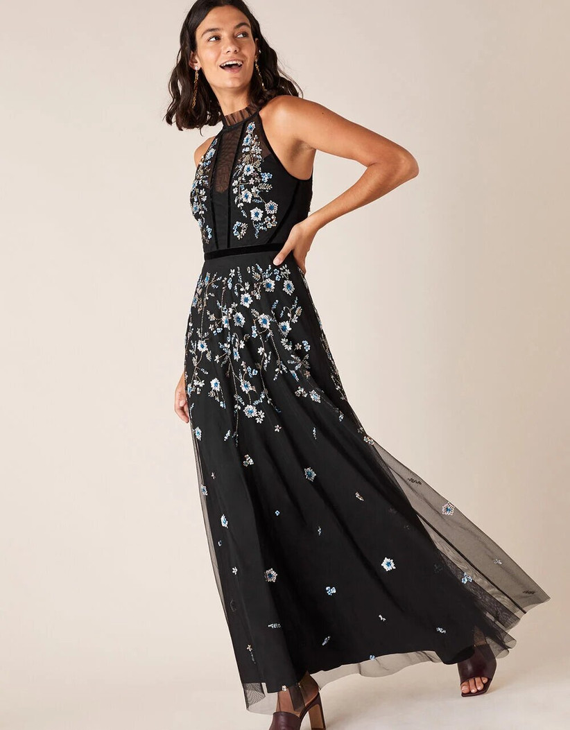 Girl wearing an embroidered halter neck black maxi dress