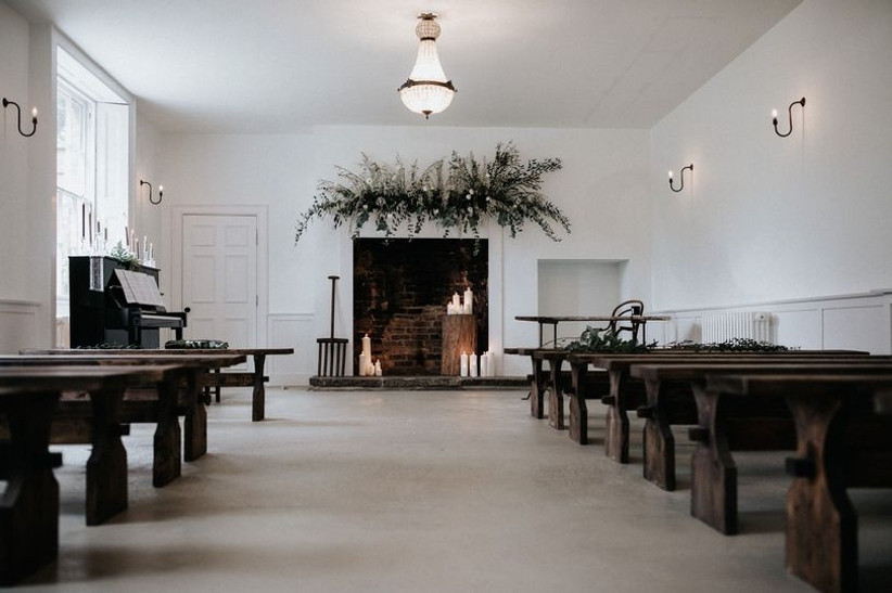 Simple wedding ceremony with wooden benches, foliage and an old fireplace