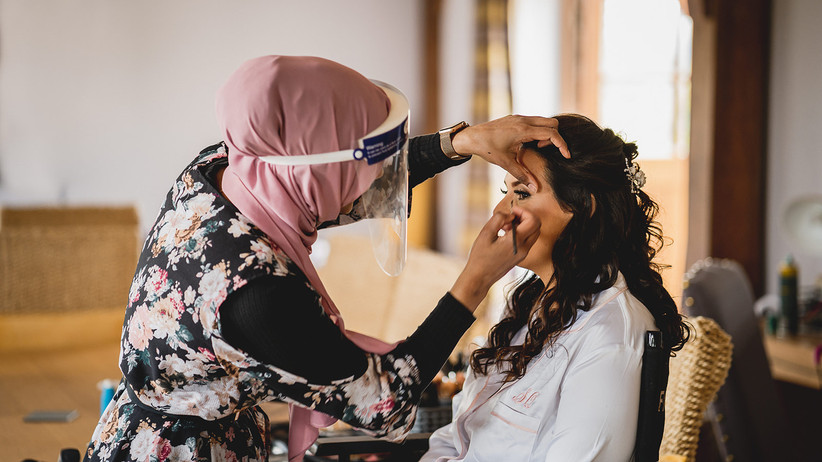 Makeup artist in a visor doing the bride's makeup