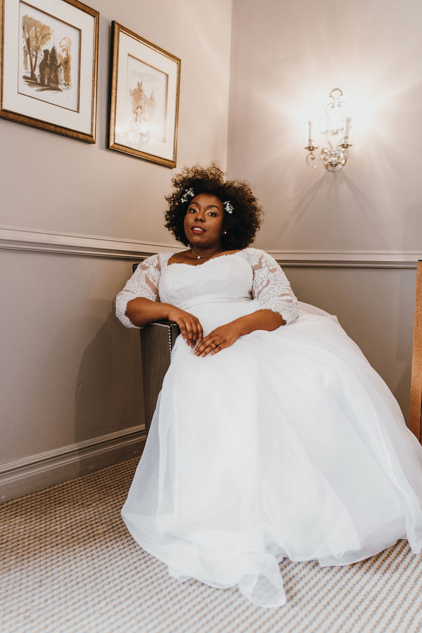 Michelle in her wedding dress sitting in a chair