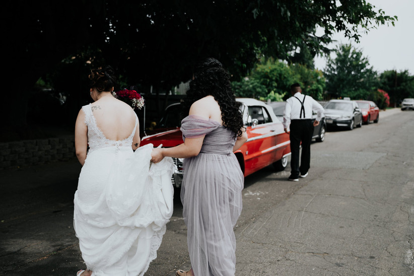 A bride walking towards a church with her dress held by a bridesmaid
