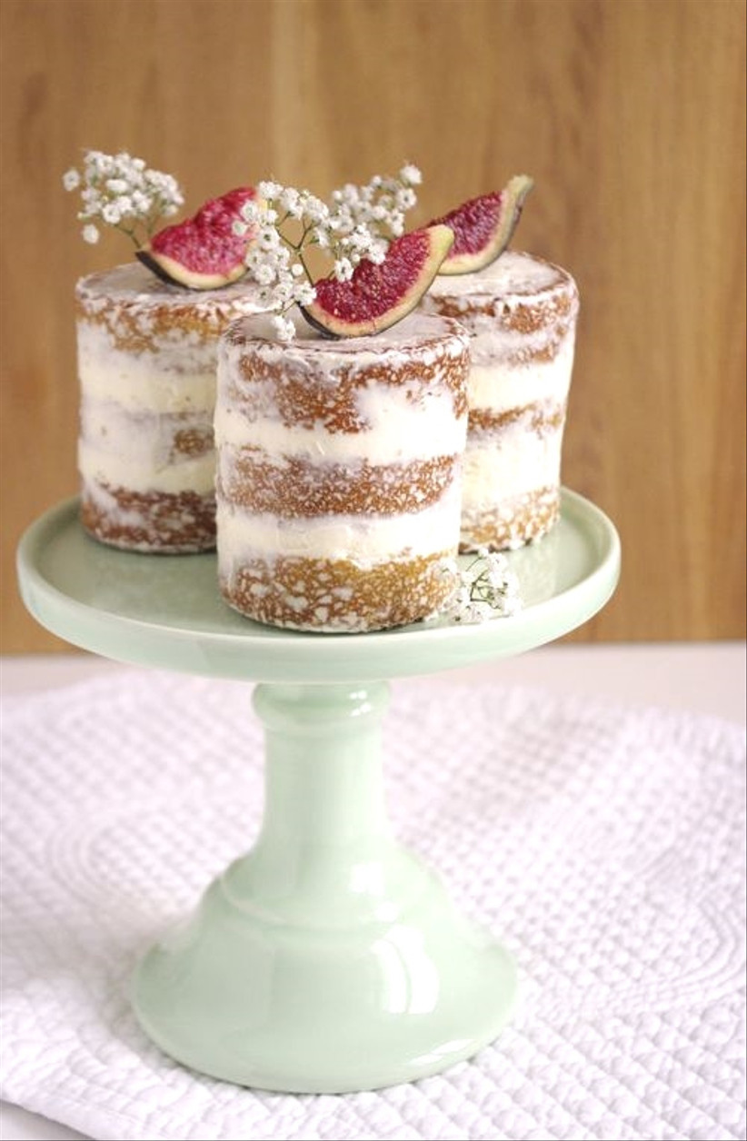 Individual semi naked rustic wedding cake topped with fruit and flowers