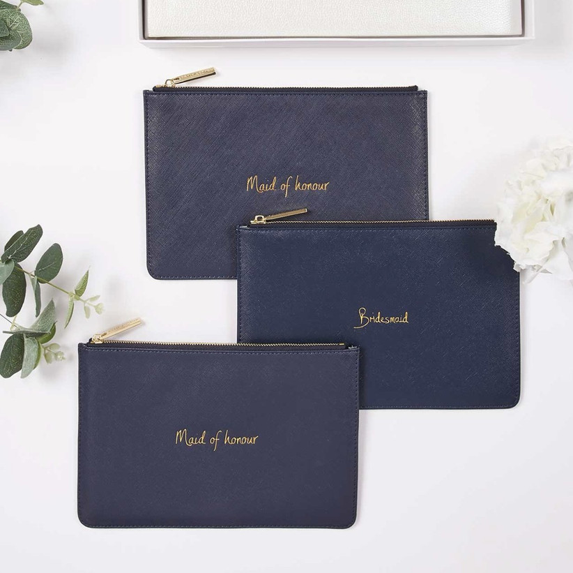 Three navy clutch bags embossed with bridesmaid and maid of honour in gold