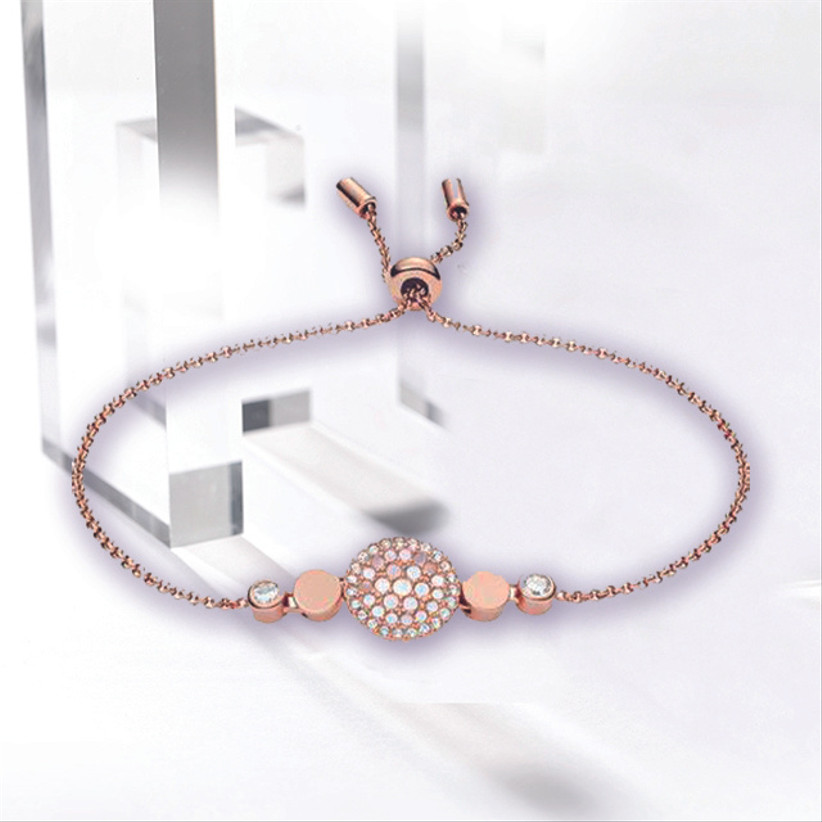 Rose gold friendship bracelet with a disc at the centre that's studded with mother of pearl