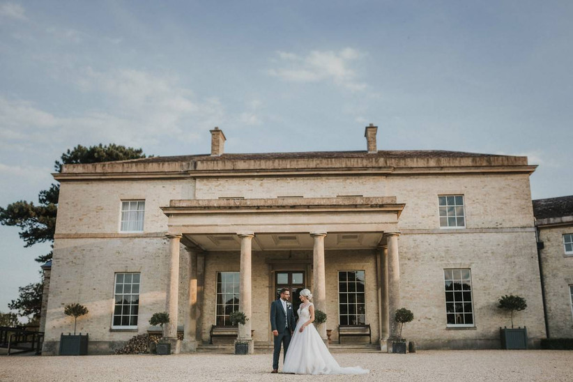 Outside view of a large country house with a bride and groom standing outside