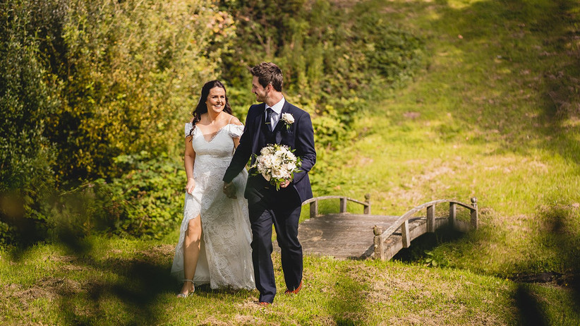 Bride and groom in a field by a bridge