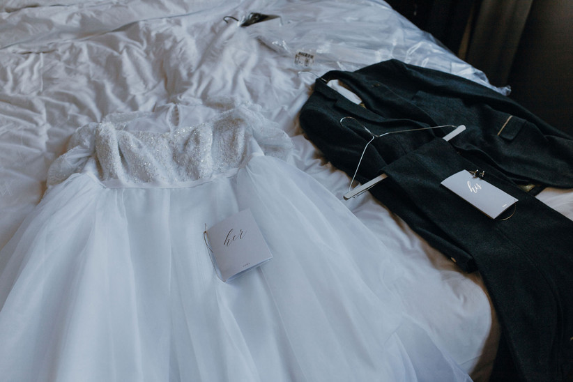 Michelle and Jonathan's wedding outfits lying on a bed