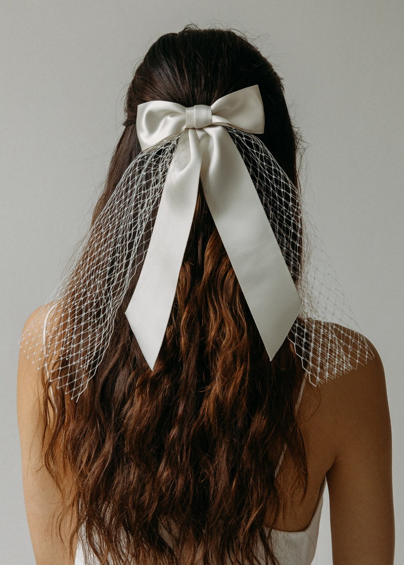 Half up half down hairstyle with white bow