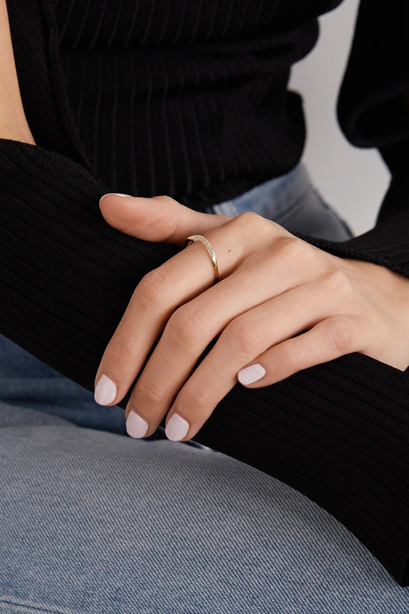 Woman wearing a black top and a pair of jeans with a pale pink manicure and wearing a curved gold ring with pave diamonds in the centre on her first finger