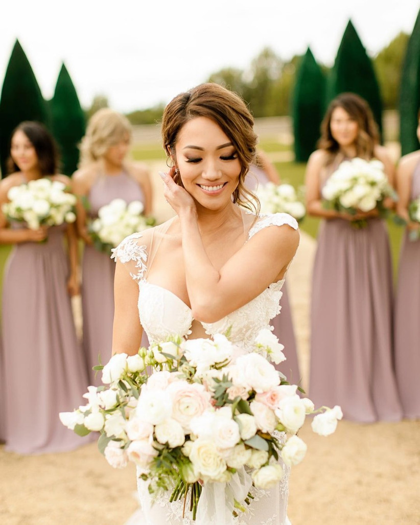 Bride standing in front of her bridesmaids holding a white bouquet