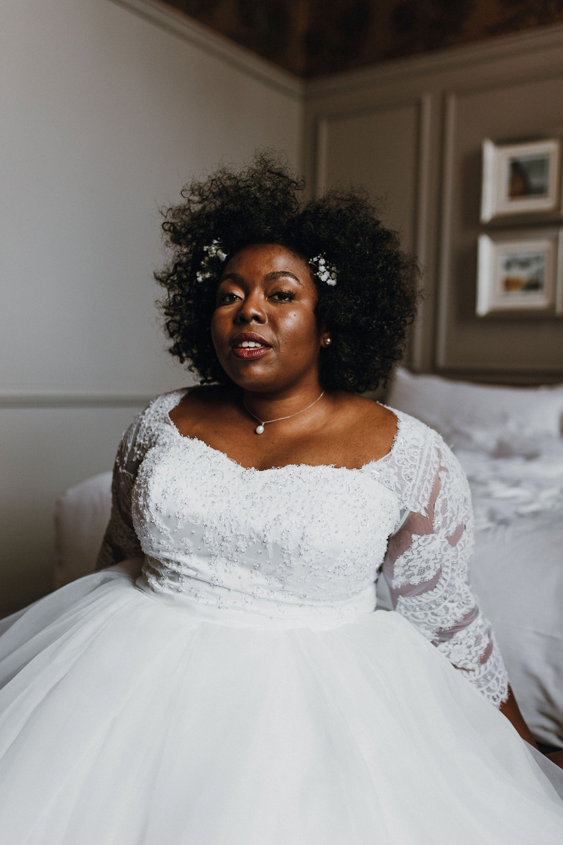 Michelle sits on the edge of a bed wearing her wedding dress