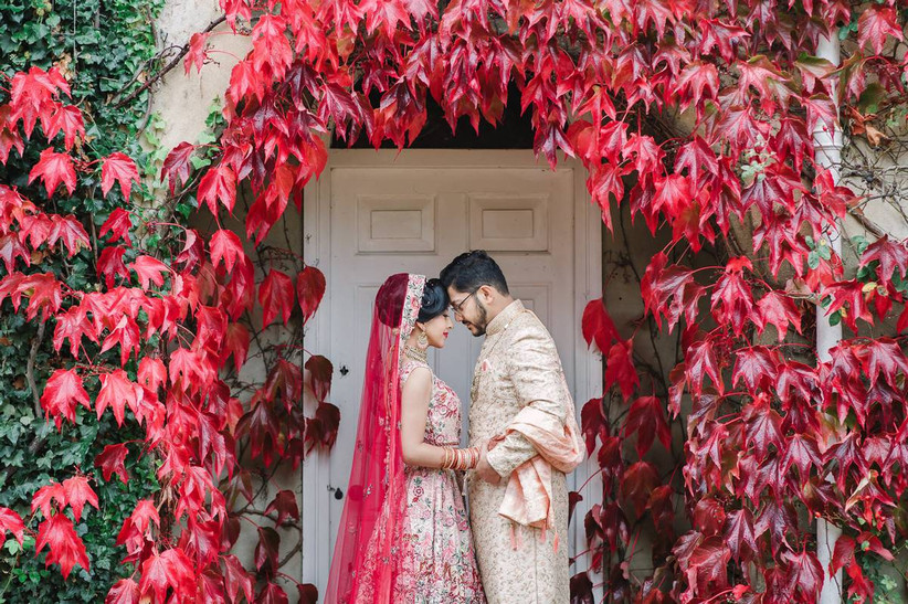 Bride and groom in front of red leaves