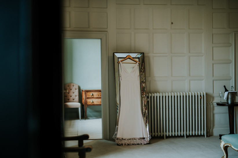Katherine's wedding dress hanging on a mirror