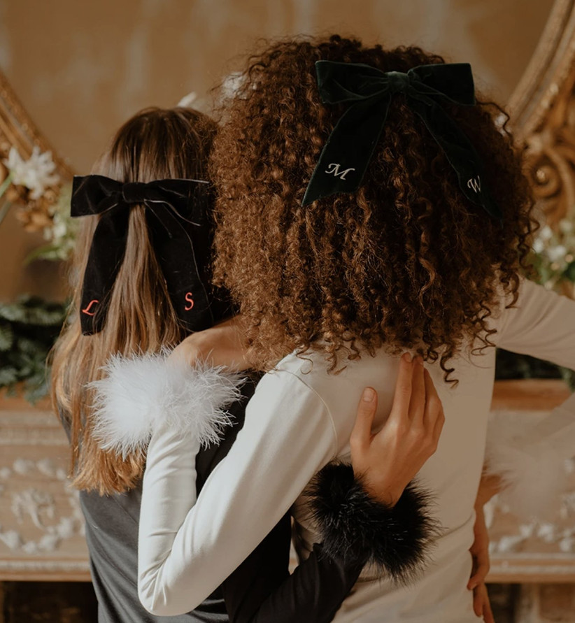 Two women with arms around each other wearing different coloured velvet ribbons in the middle of their hair embroidered with individual initials