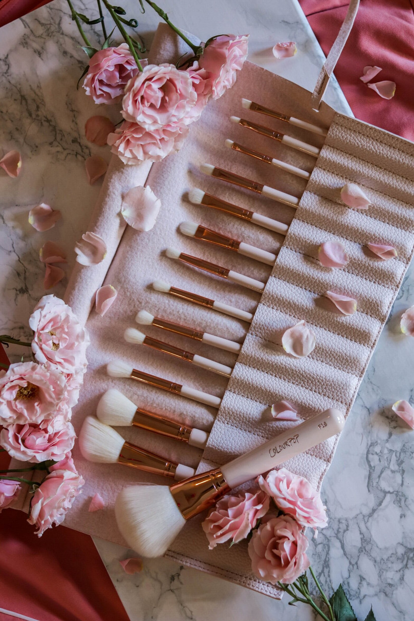 Pink makeup brushes laid out with rose petals