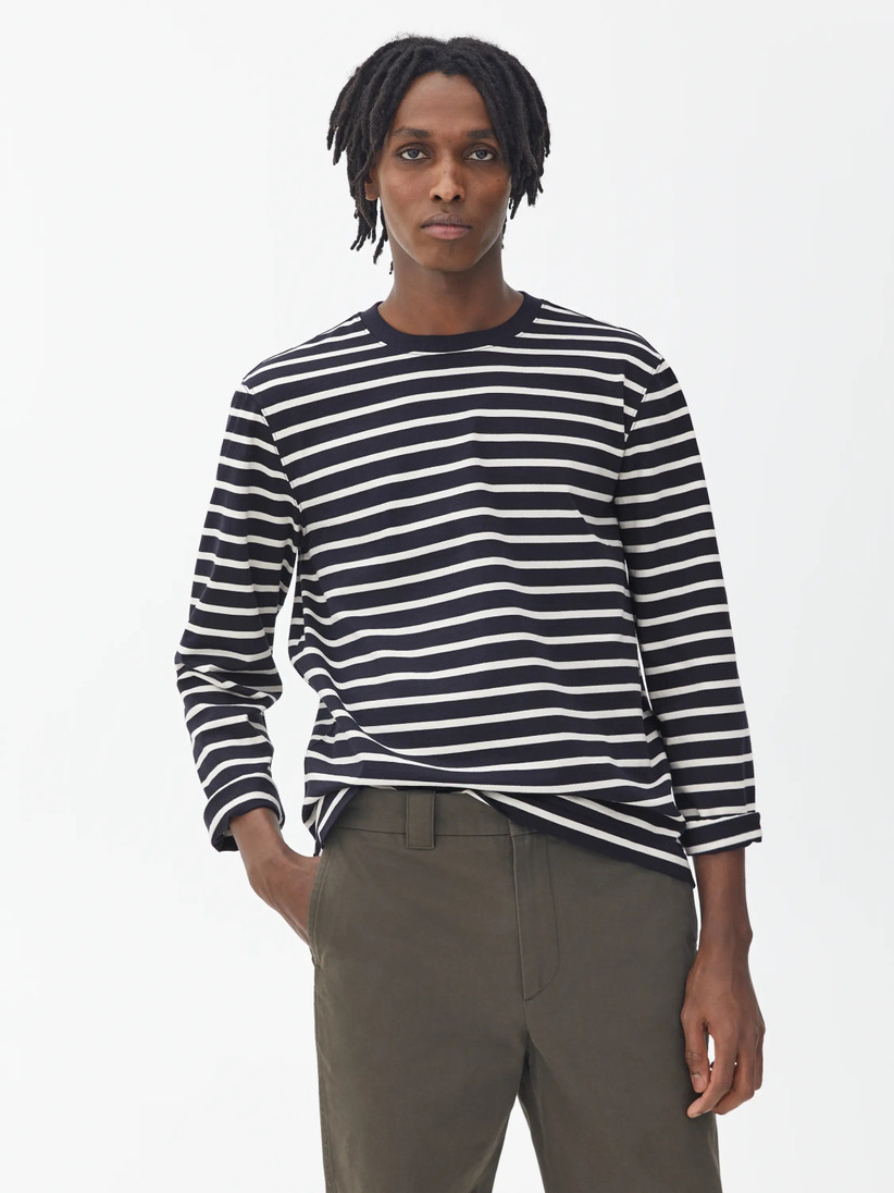 Black man with fine dreadlocks wearing a navy and blue striped long sleeved t-shirt and khaki trousers