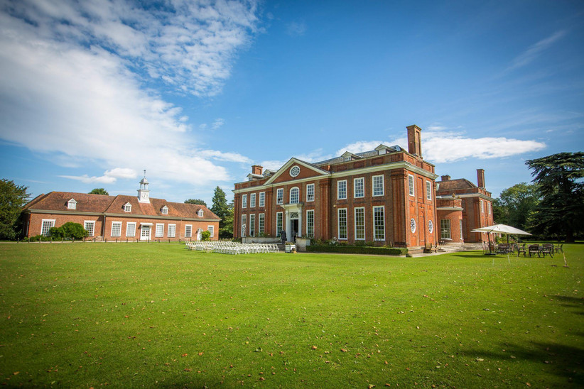 Exterior of country manor Bradbourne House on a sunny day, with green lawn stretching out in front of the main building