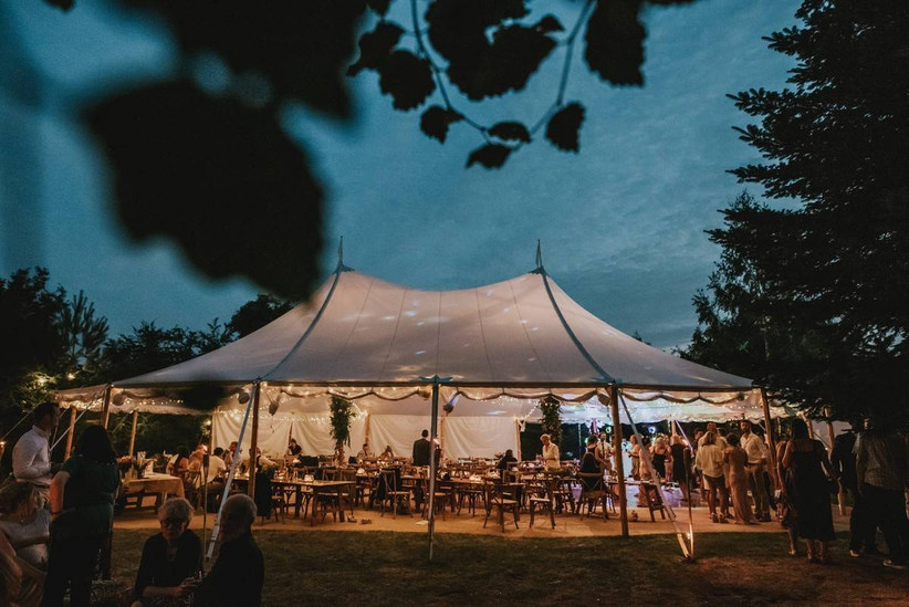 Marquee in the evening with wedding guests celebrating