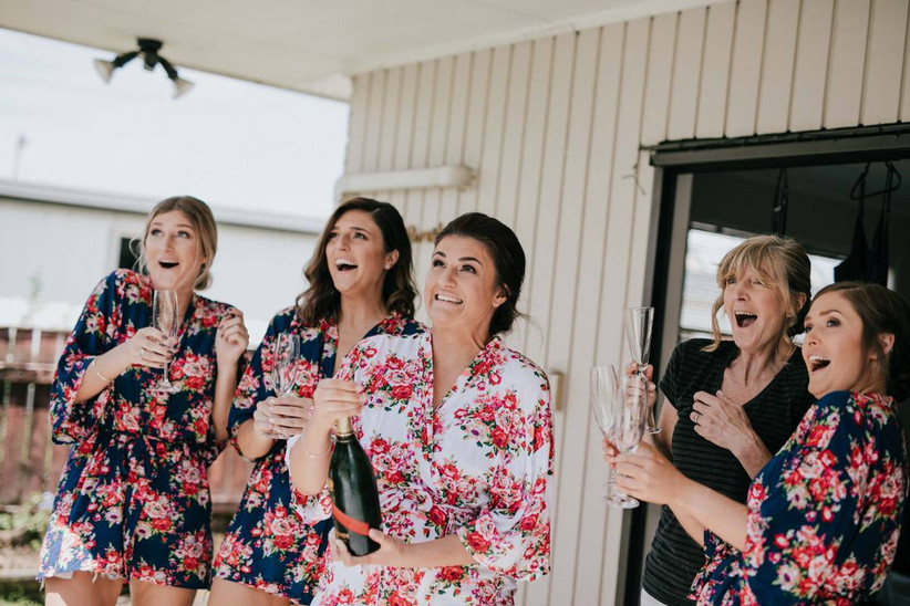 Bride pops champagne while her bridesmaids watch
