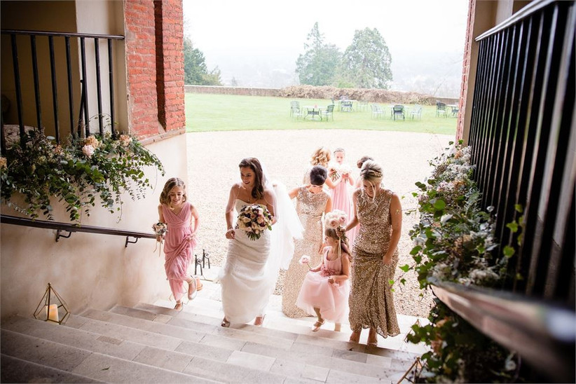 Bride and bridesmaids walking up a staircase decorated with flowers