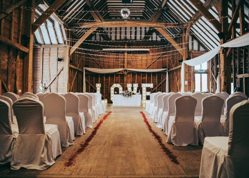 Barn ceremony room with white chairs and fairy lights