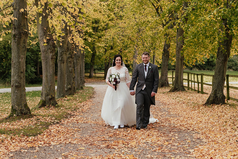 Becky and Ben walking hand in hand along a tree-lined avenue