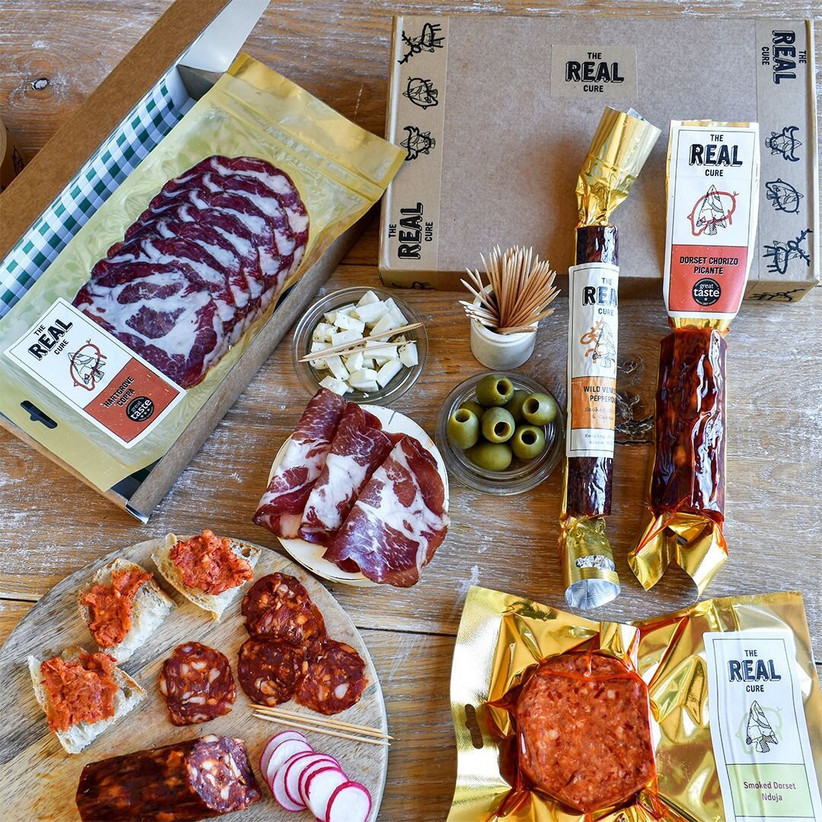 Selection of cured meats, cheese, olives and cocktail sticks displayed on a wooden table