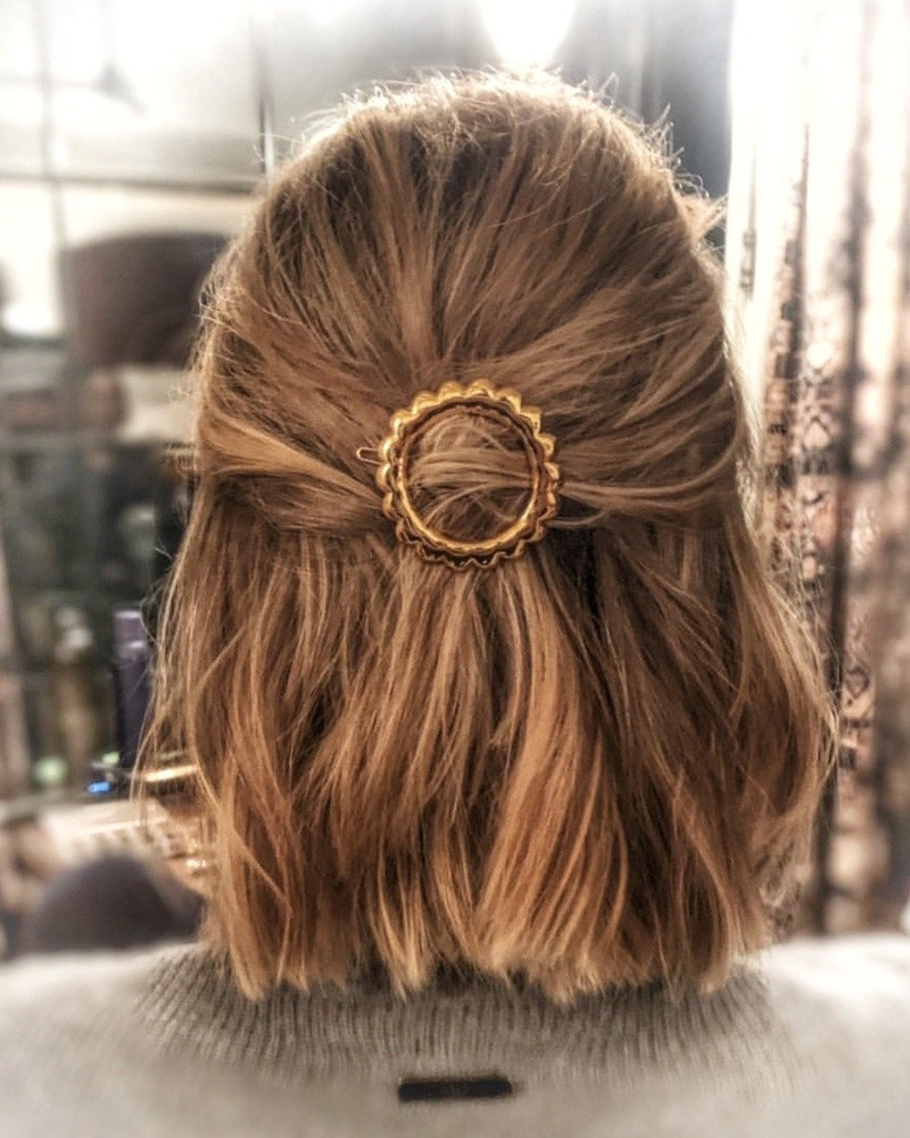 Short half up half down hairstyle with gold ring clip