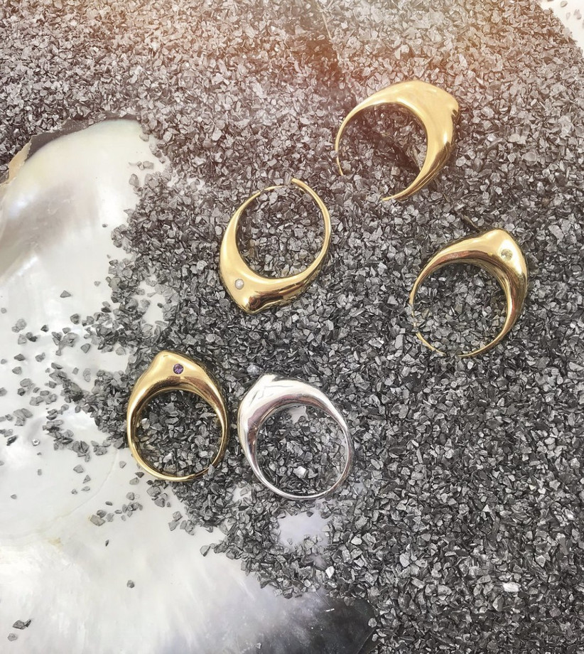 Four gold sculptural style rings studded with a single different coloured gemstone on a stony beach with sea foam to the lift