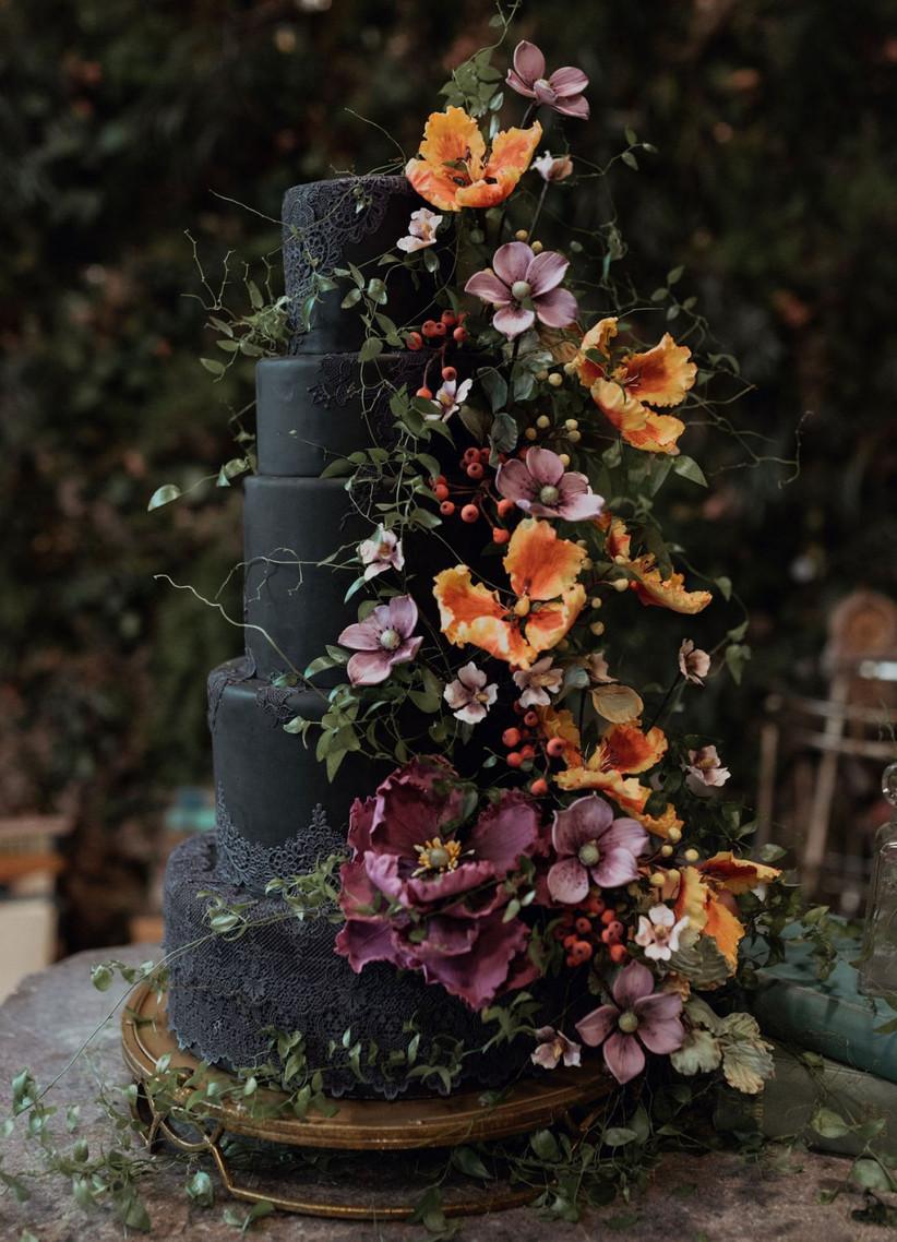Five tiered black rustic wedding cake with orange flowers