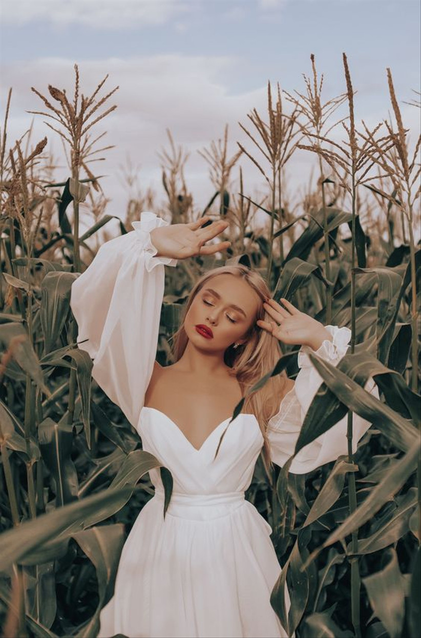 Girl with her eyes closed and arms up standing in a corn field
