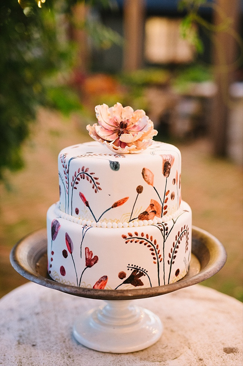 Two tiered white fondant rustic wedding cake with hand painted flowers