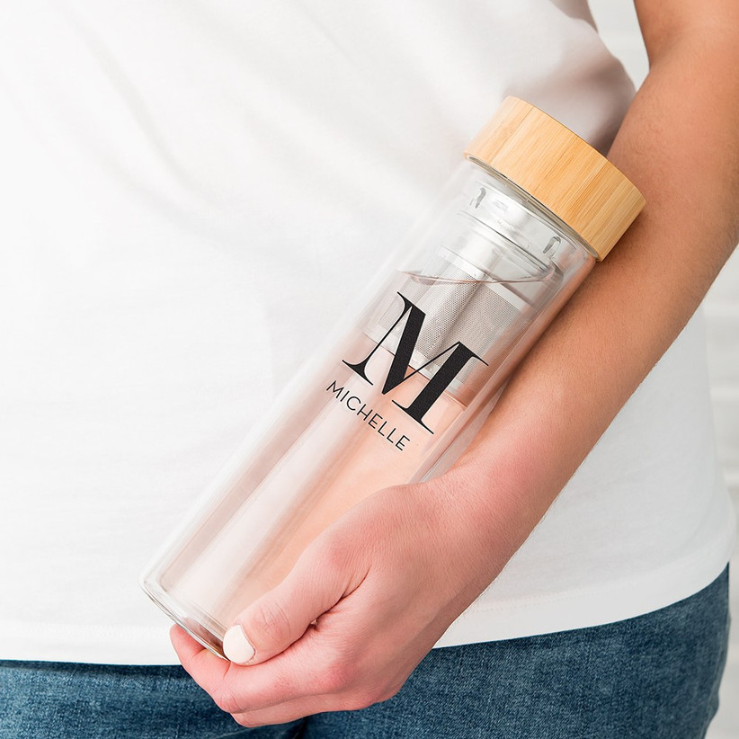 Woman holding a clear infuser mug with a wooden top personalised in black with a single M initial and the name Michelle underneath
