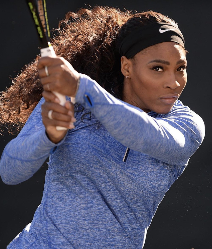 Serena Williams swinging a tennis racket wearing a blue top and Nike headband