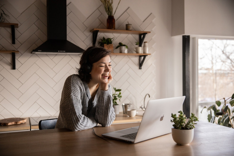 Woman wearing a grey jumper sitting at a kitchen table talking at a silver Macbook