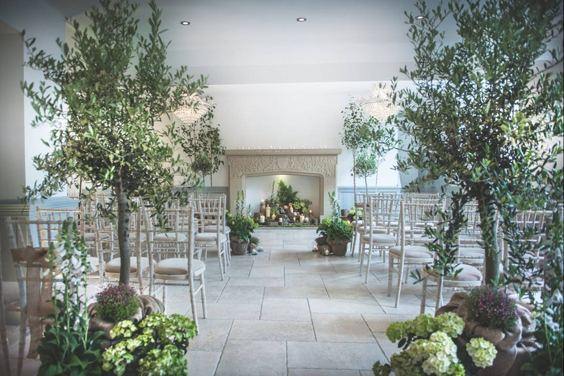 Wedding ceremony with fireplace decorated with trees and greenery