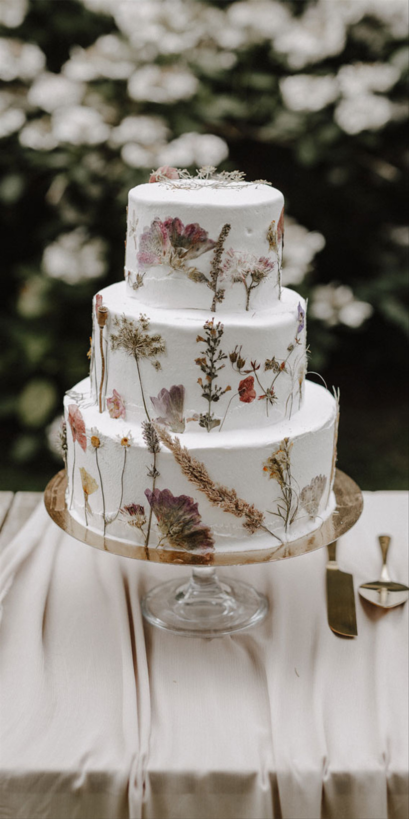 Three tiered white fondant rustic wedding cake with dried flowers