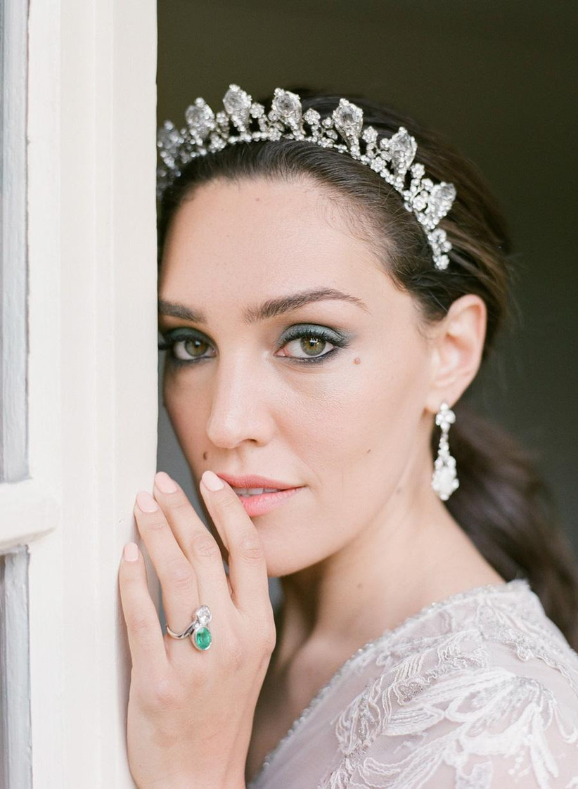 Bride with tiara leans on a window frame