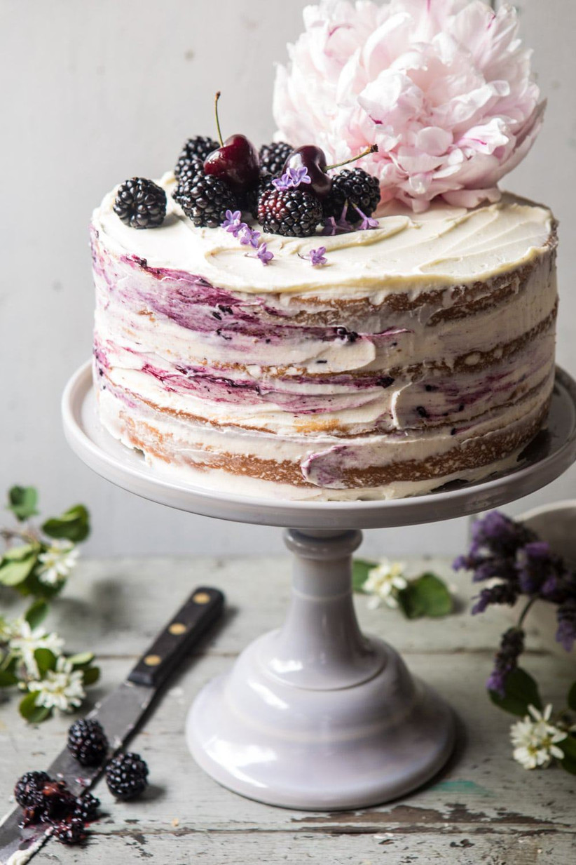 Semi naked rustic wedding cake with smears and blackberries