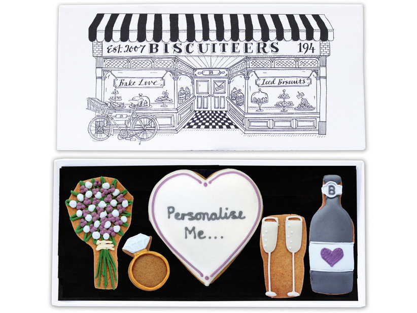 Small box filled with iced biscuits depicting a bunch of flowers, a diamond ring, two champagne glasses and a bottle of champagne and a personalised heart biscuit in the centre