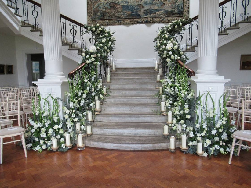 Grand staircase decorated with white flowers and candles